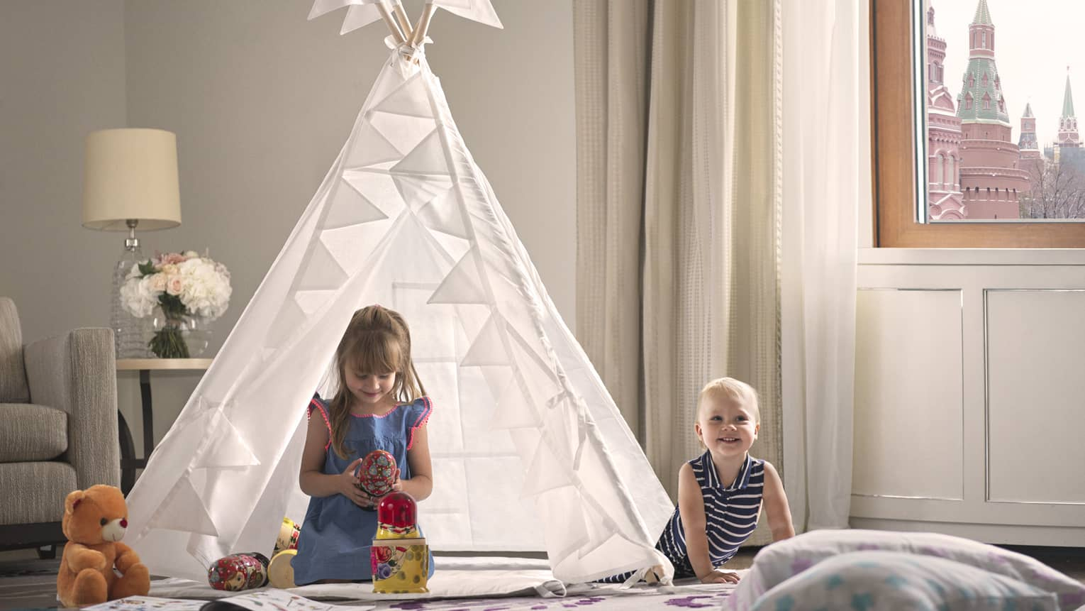Two little girls play in a child's teepee in a four seasons hotel room