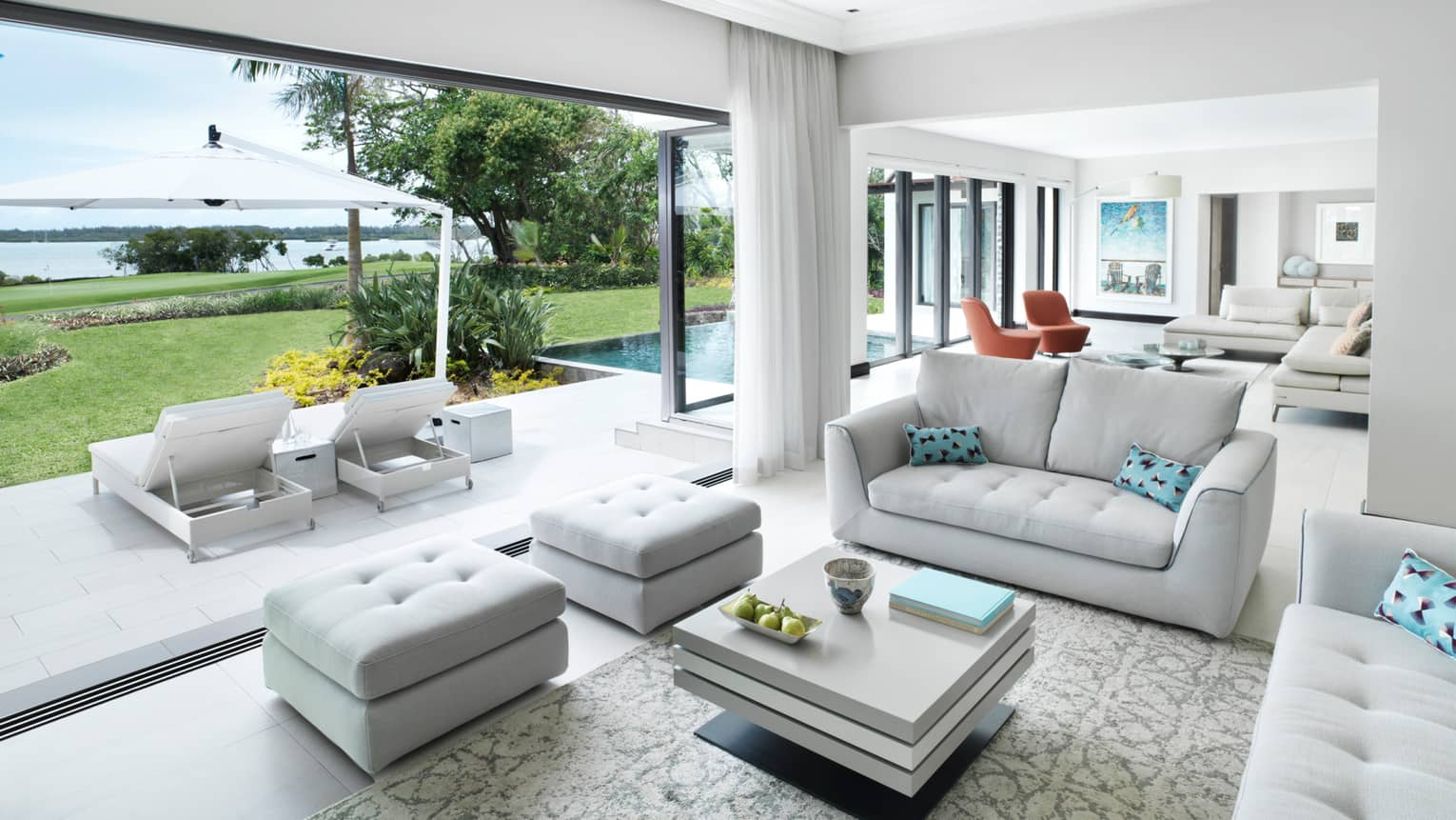 Suite with two white sofas, aqua pillows, two ottomans, square coffee table, patio and water view