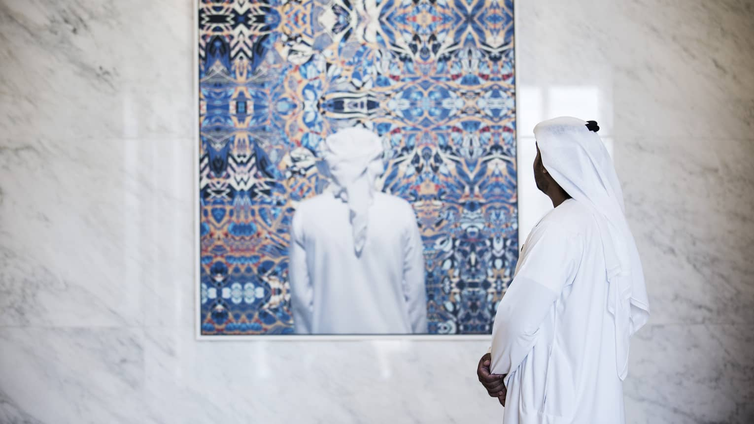 Side view of man dressed in white looking at colourful painting on white marble wall
