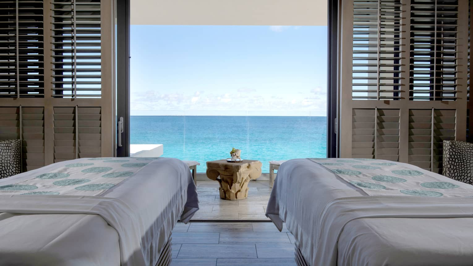 Couples massage beds in private spa cabana looking out at the ocean
