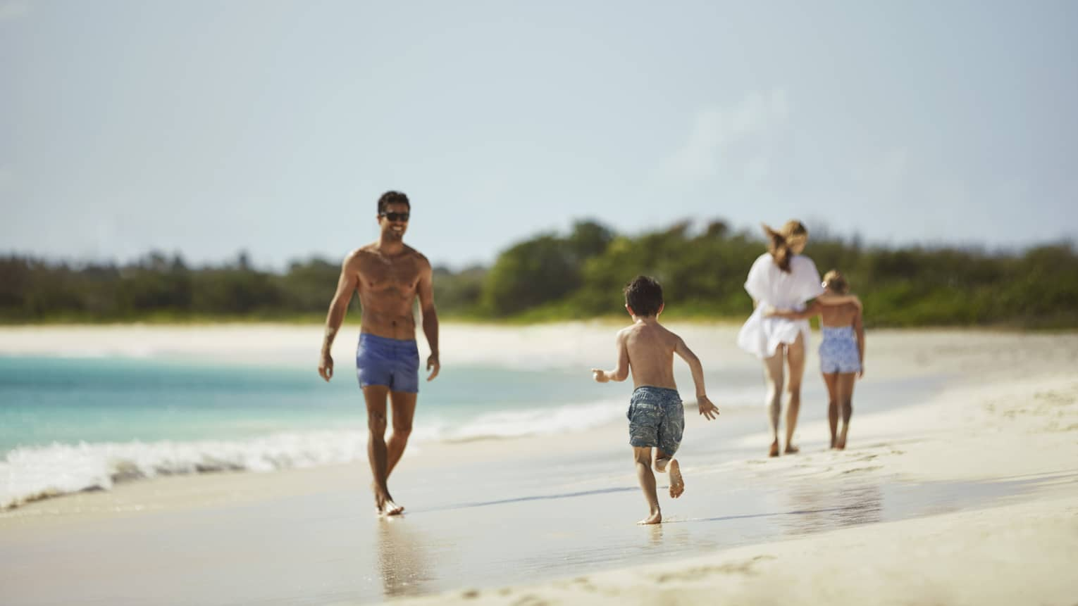 Family runs, plays on sand beach by ocean