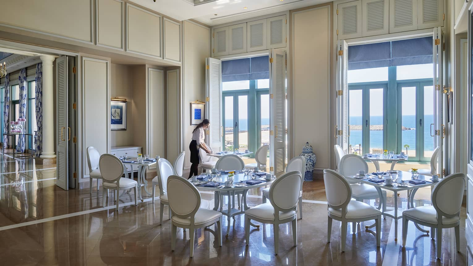 Server sets white table at Kala restaurant, white shutters with blue blinds lead to ocean views