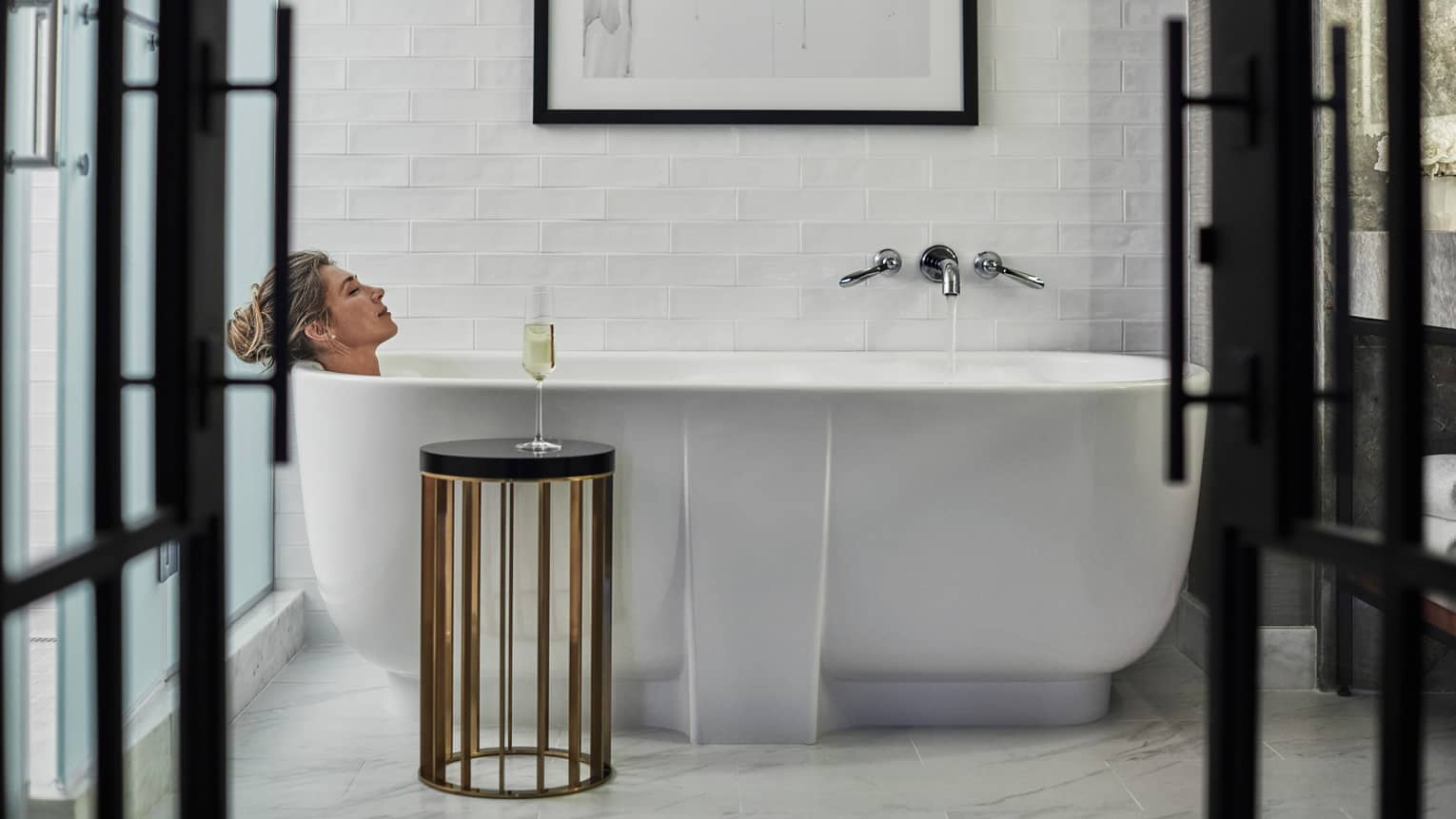 Woman leans back in large freestanding white tub, glass of white wine on stool
