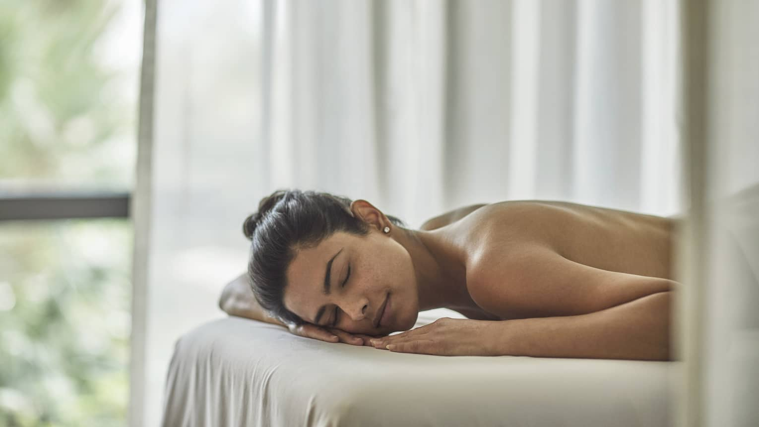 A woman relaxes on white sheets in preparation of a spa treatment