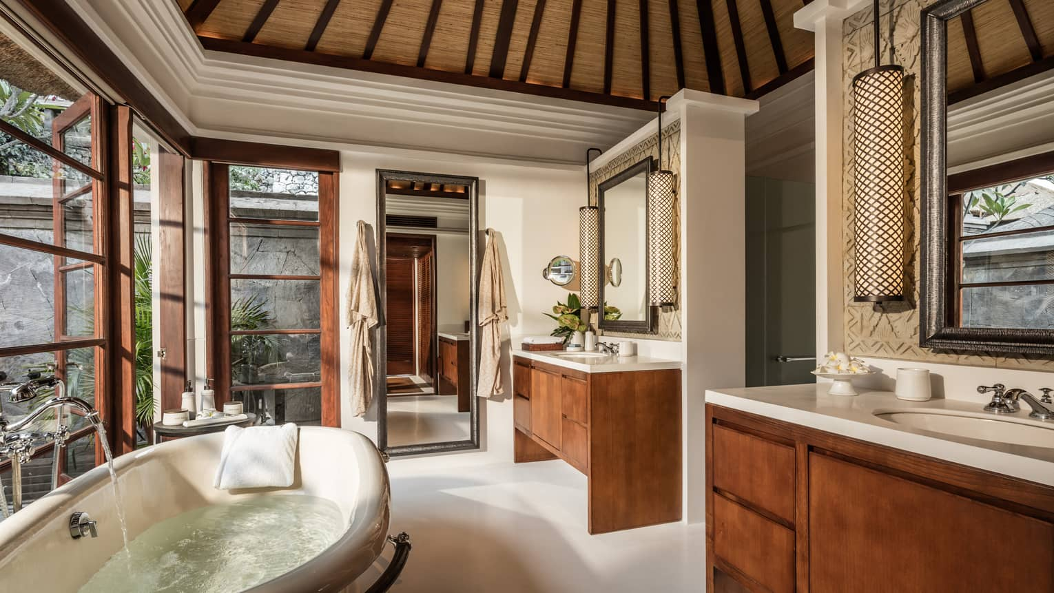 Water runs from faucet into deep tub in Imperial Villa bathroom with double wood vanities, mirror