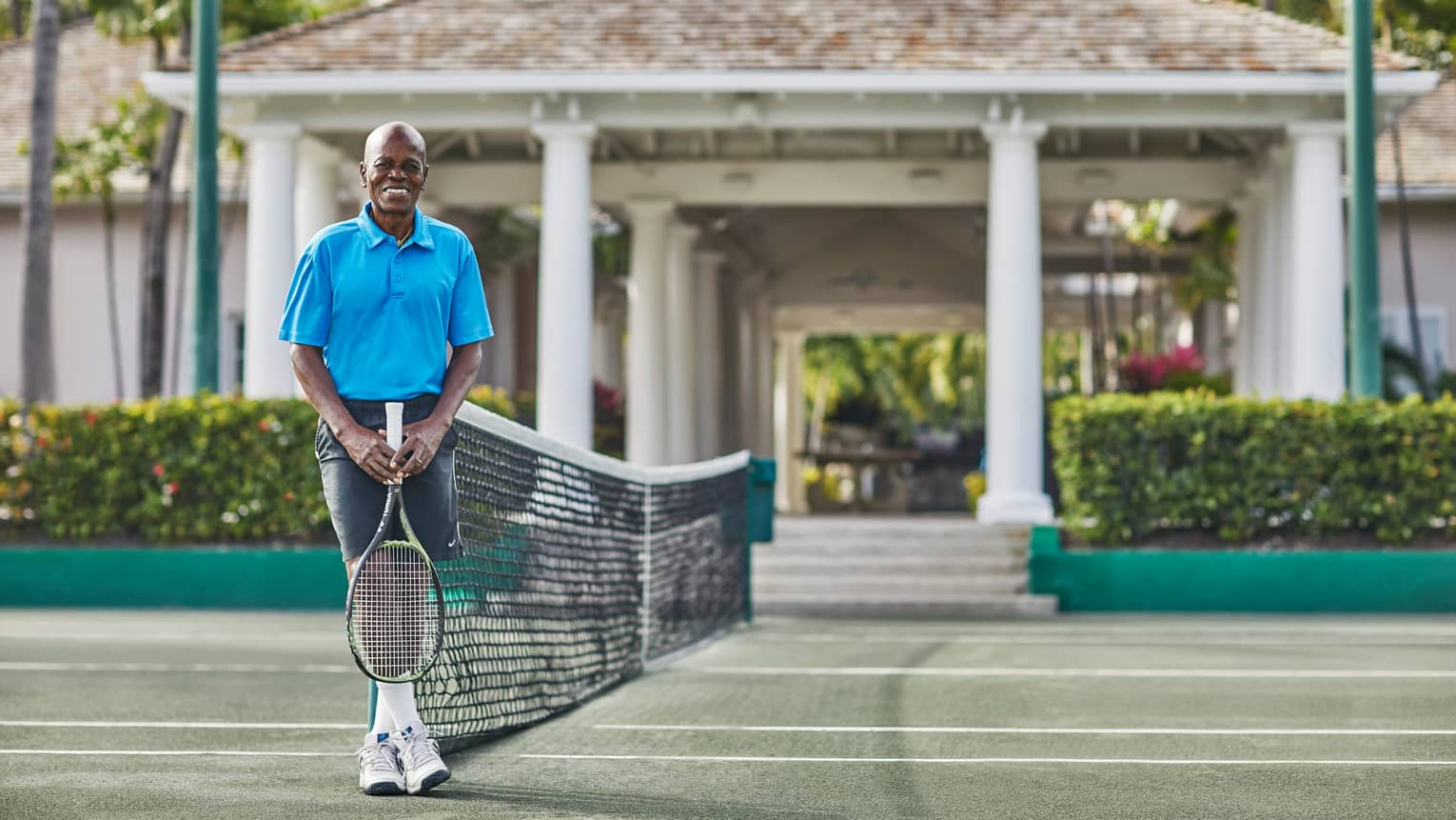 Tennis pro Leo Rolle holds racket, stands against net on sunny tennis court