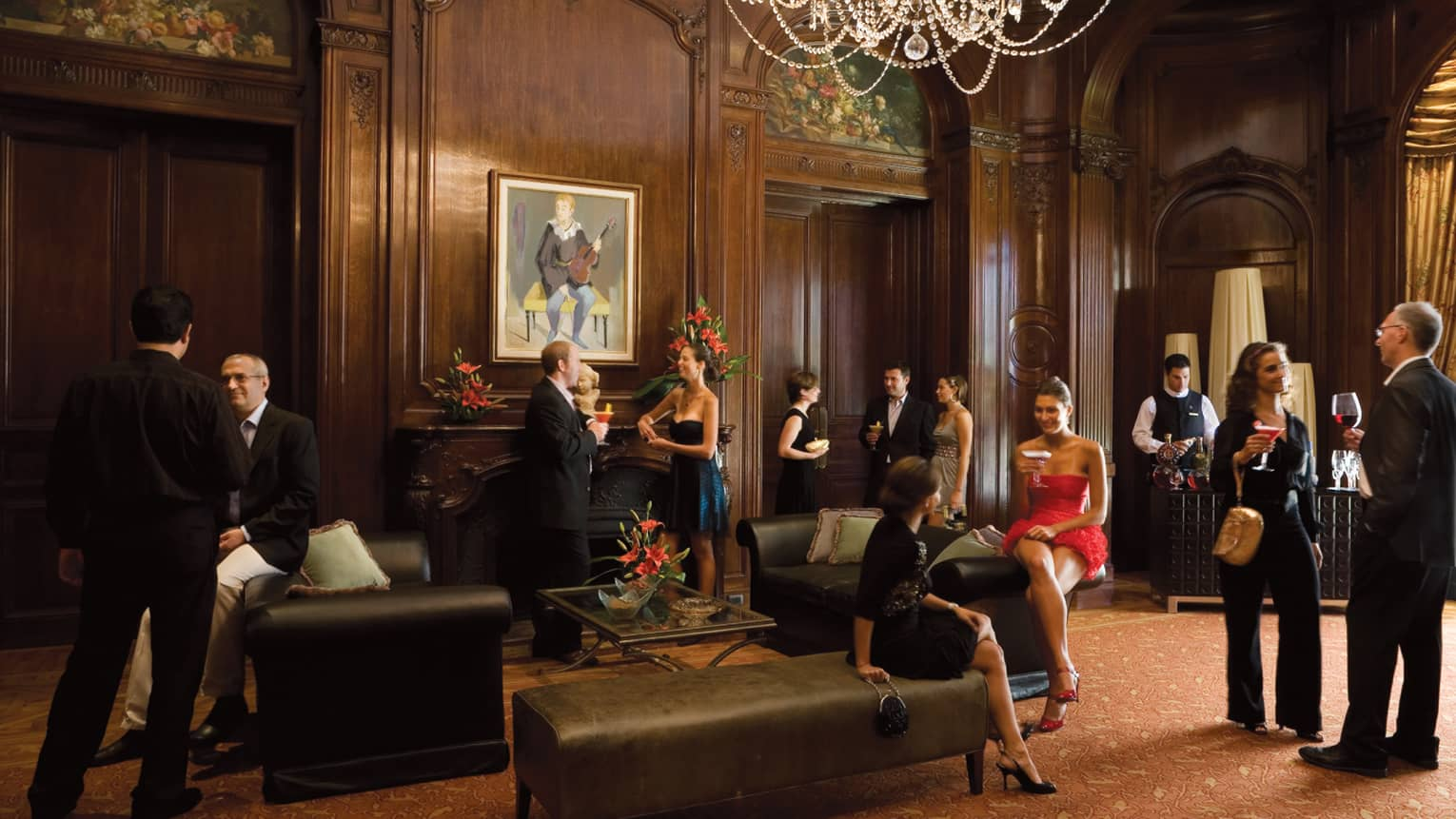 People wearing cocktail attire socialize in elegant ballroom with wood walls, crystal chandelier, leather benches