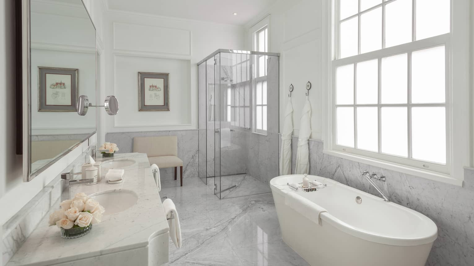 The La Mansion Bathroom is filled with a porcelain bath tub, glass shower and long mirror