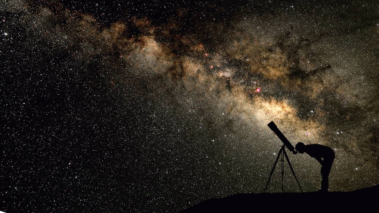 Silhouette of stargazer leaning into telescope against a starry sky, milky way