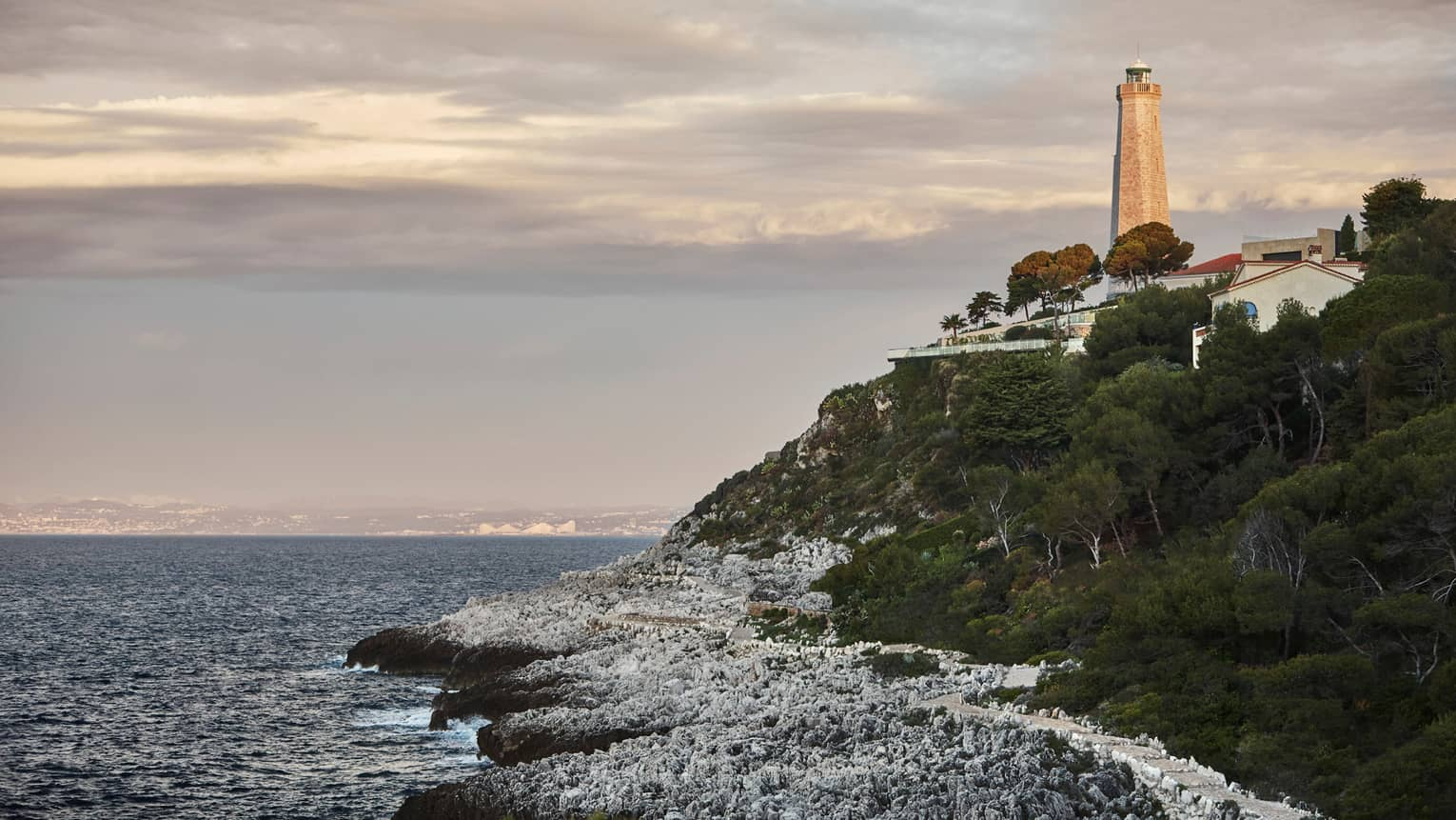 Stone lighthouse tower on rocky green cliff over crashing waves, sea