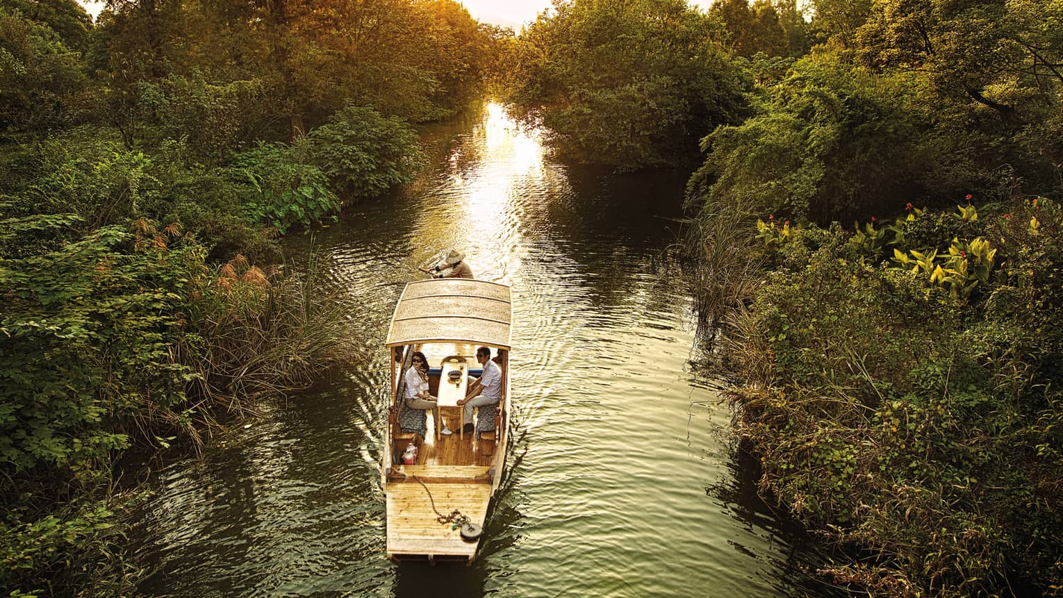 Couple in Chinese wooden row boat travelling through West Lake marsh