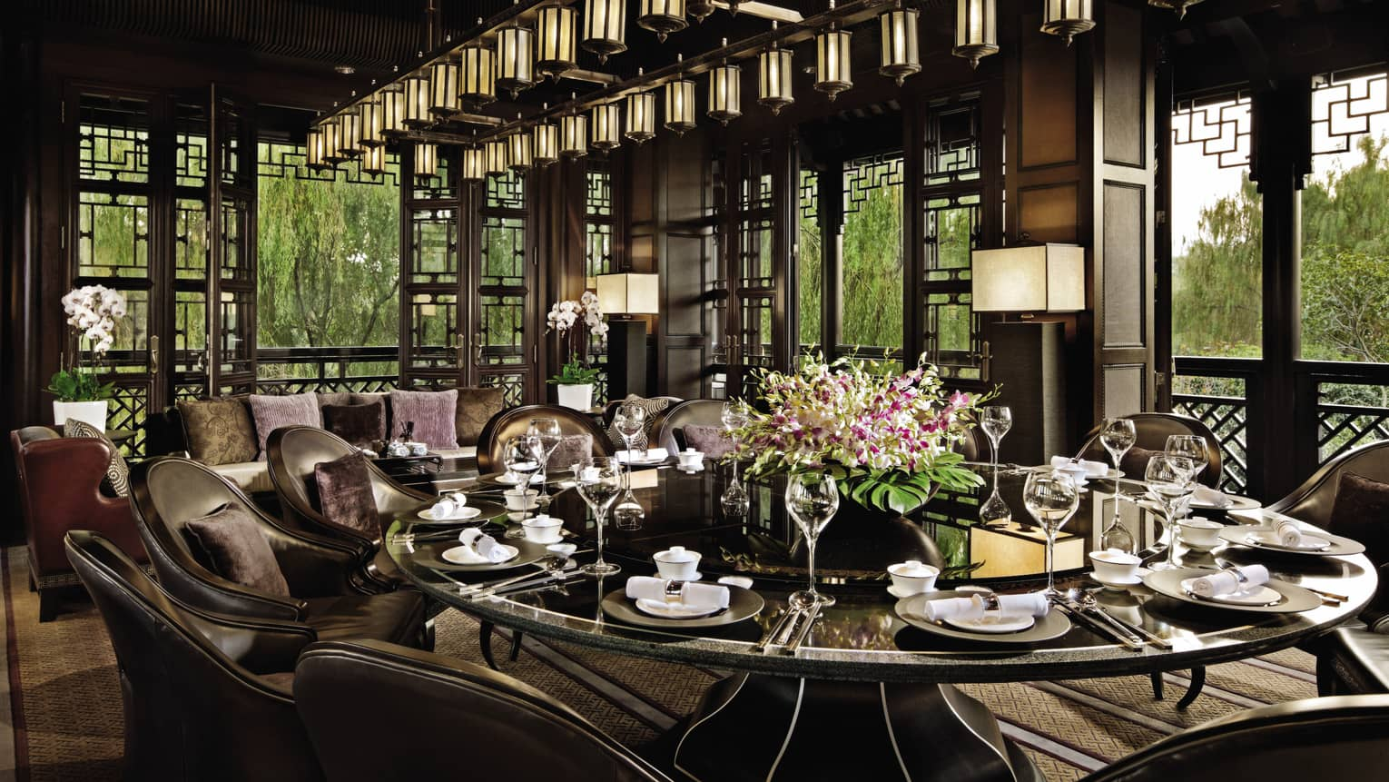 Large round, black, shiny dining table under lantern chandelier at Jin Sha