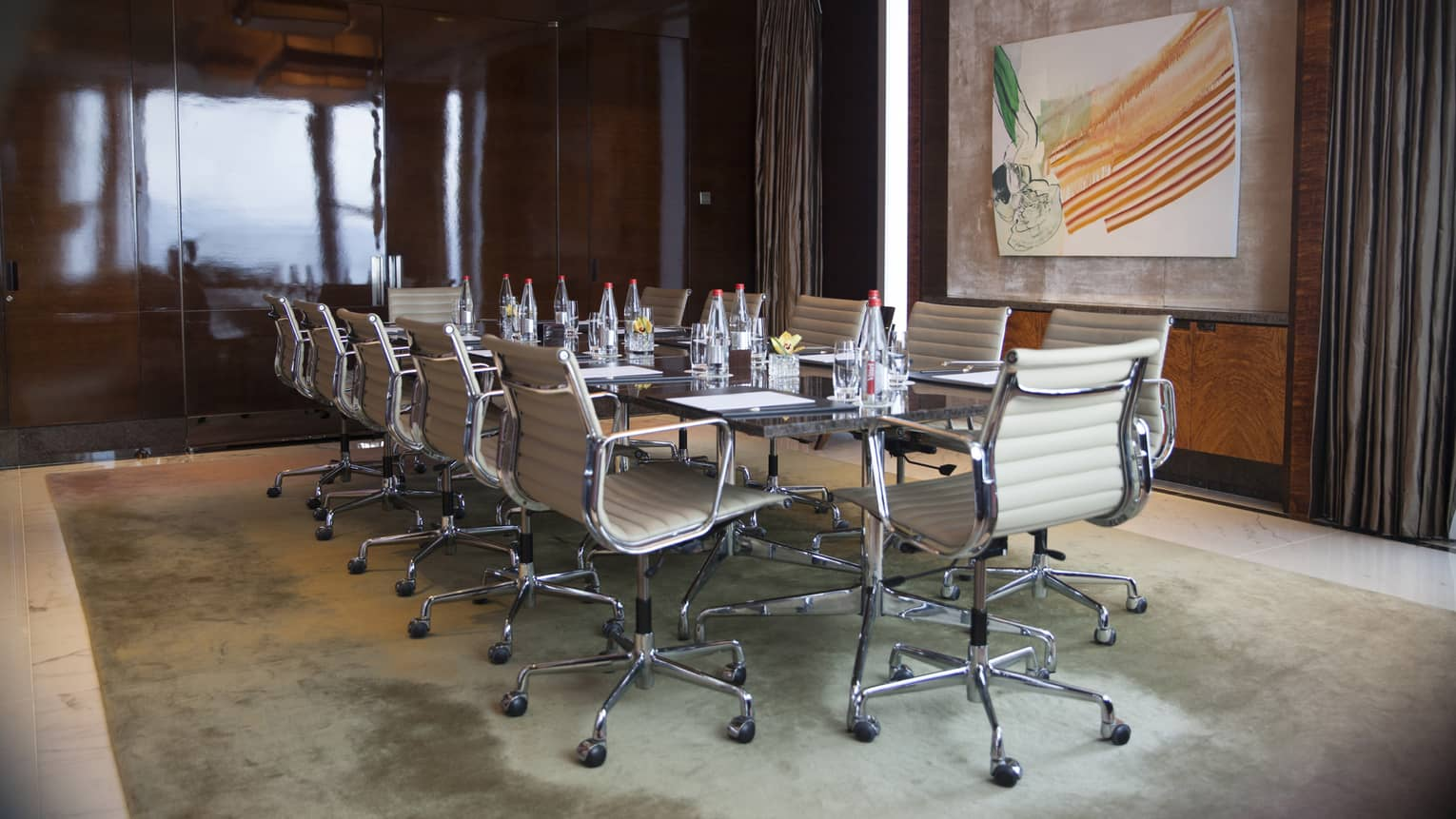 Meeting room with boardroom table, white leather swivel chairs and modern art painting