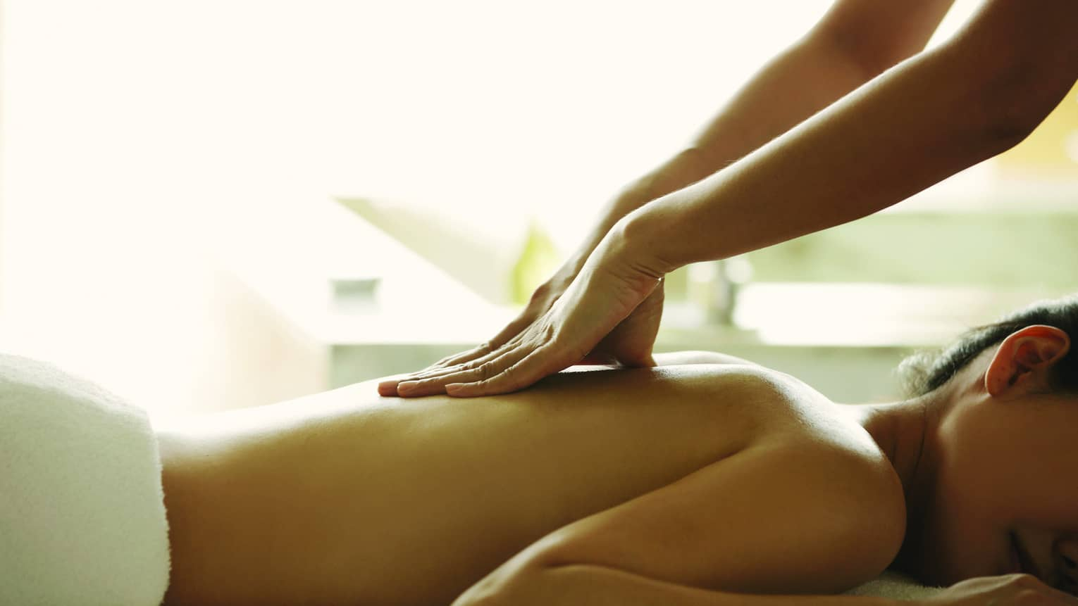 Masseuse reaches over, massages woman's bare back as she lies on spa table