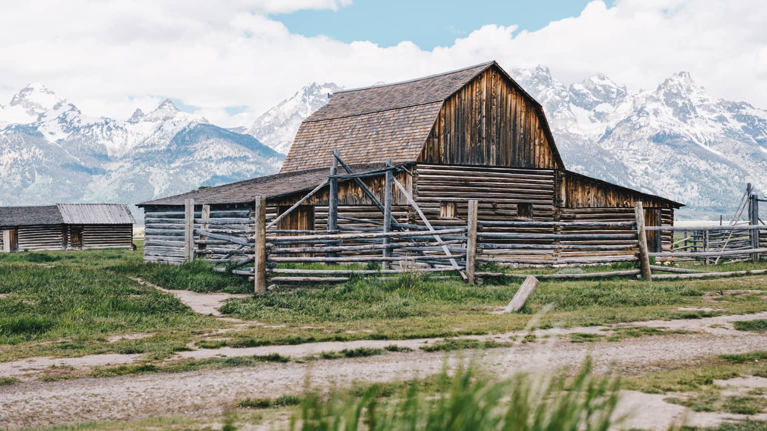 An old barn sits on a grassy patch of land, the snow-capped mountains looming behind it