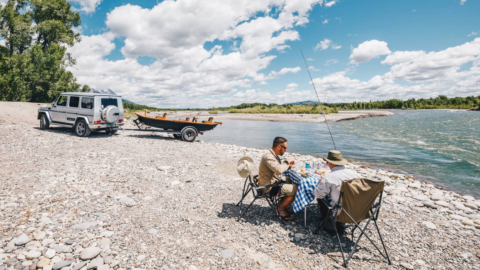 Two fishermen sit at a small table for a lakeside picnic, their boat hitched to their SUV in the background