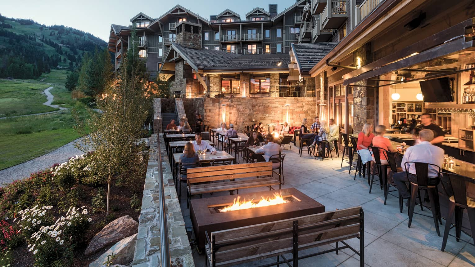 Outdoor patio of Handle Bar restaurant/pub with firepit, tables and bar seating with mountain view