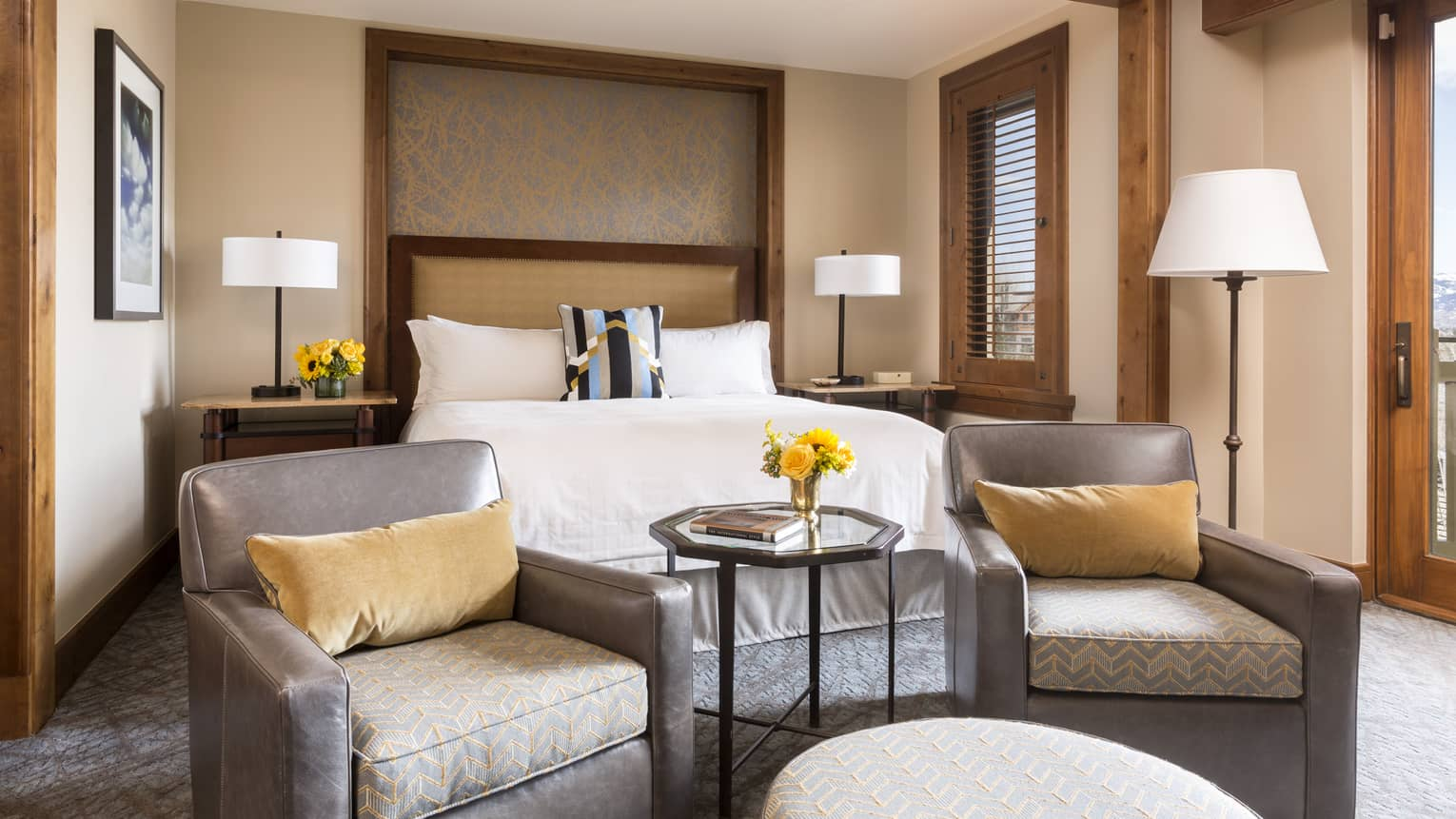 Valley-View Room grey armchairs with yellow velvet pillows in front of bed, lamps
