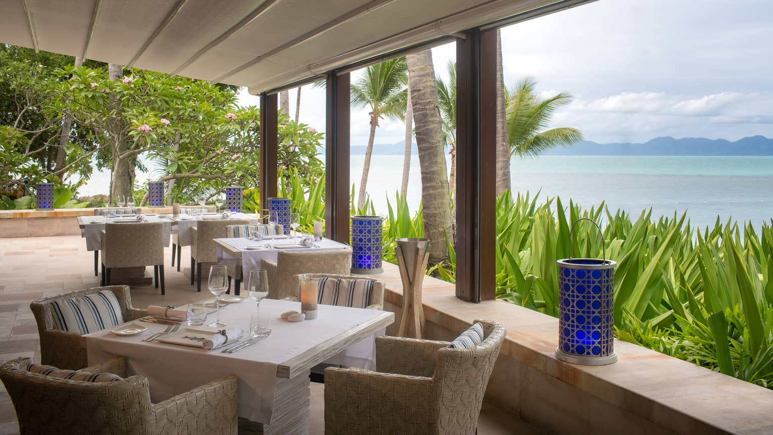 square tables overlooking the ocean are set for dinner