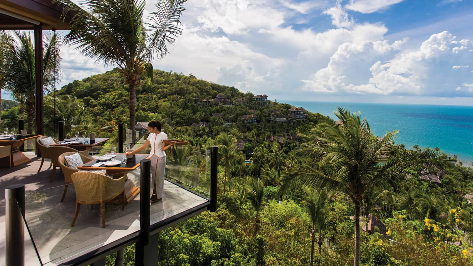Server sets corner patio table behind glass balcony, high on tropical mountain