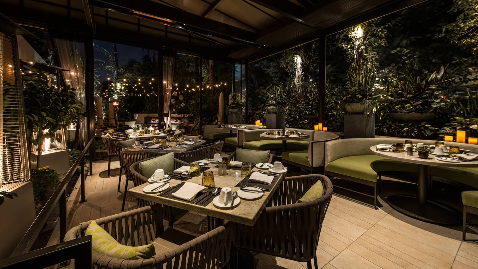 Culina Restaurant dining patio, plush green and grey dining chairs, booths under awning at night