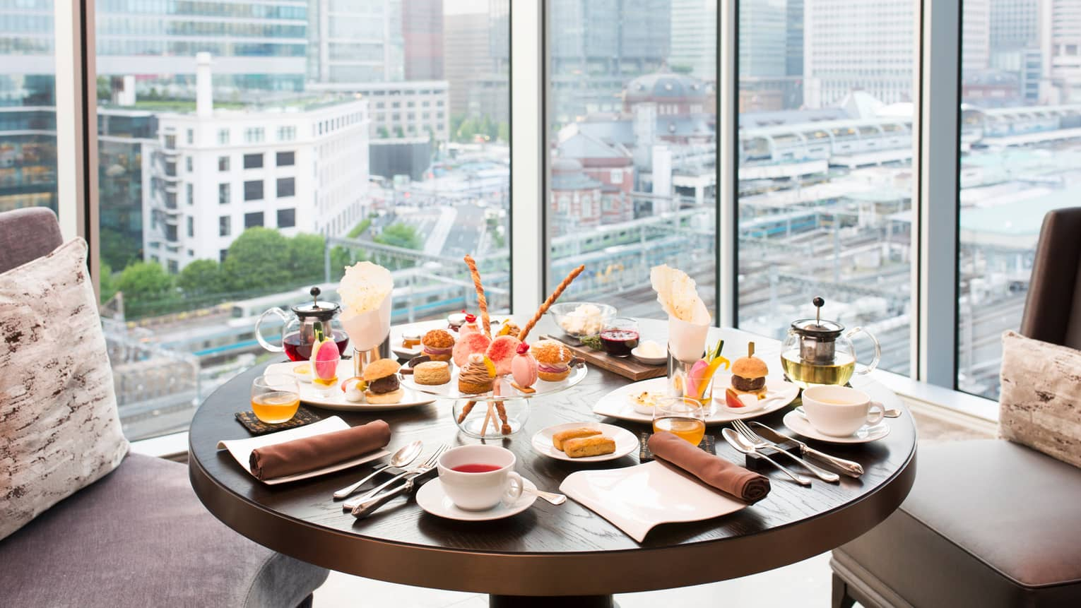 Round table with Afternoon Tea cakes, pastries in front of sunny window overlooking Tokyo Station
