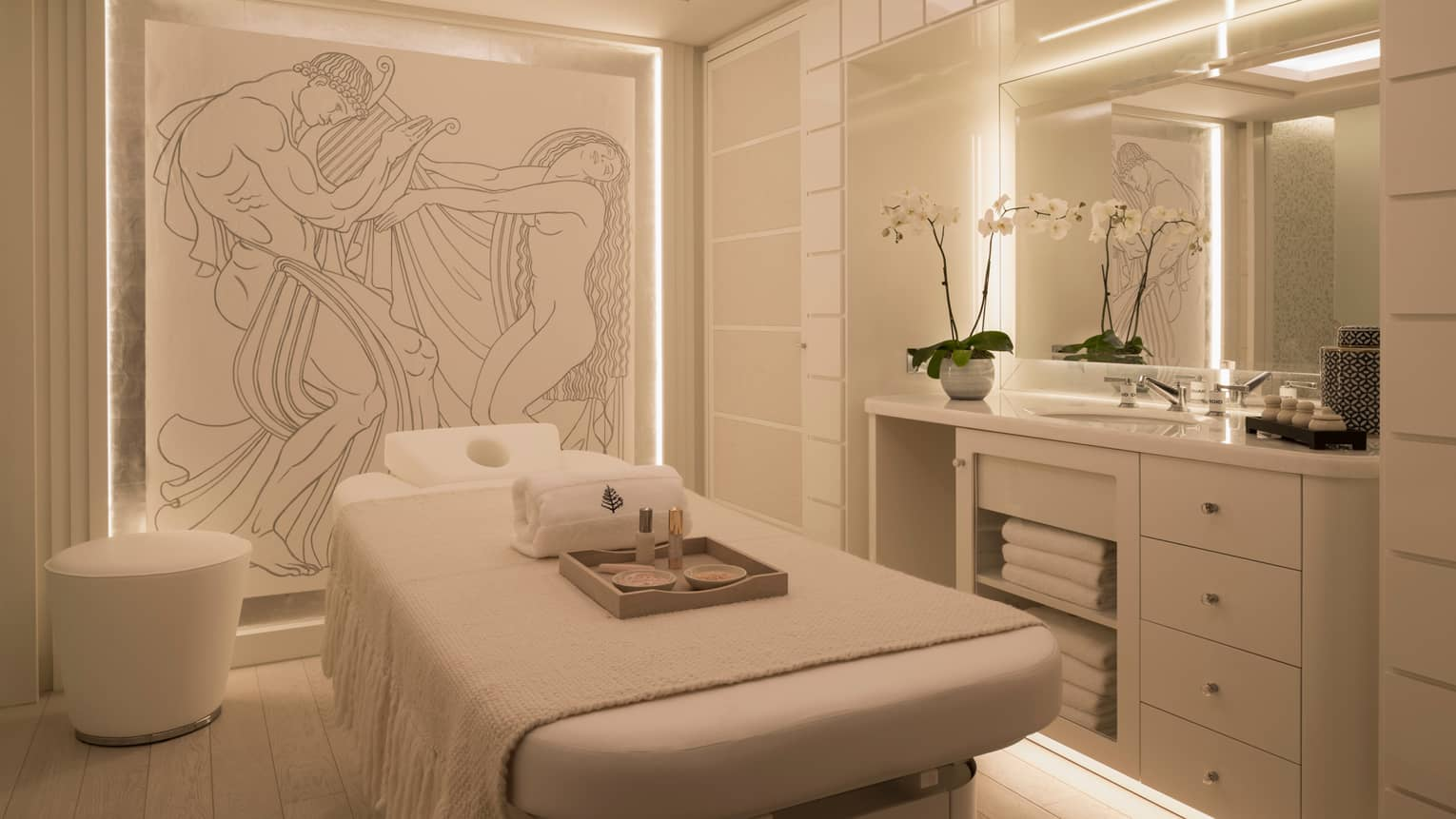 VIP Spa Treatment Room bed with tray, towels under mural, orchid on vanity