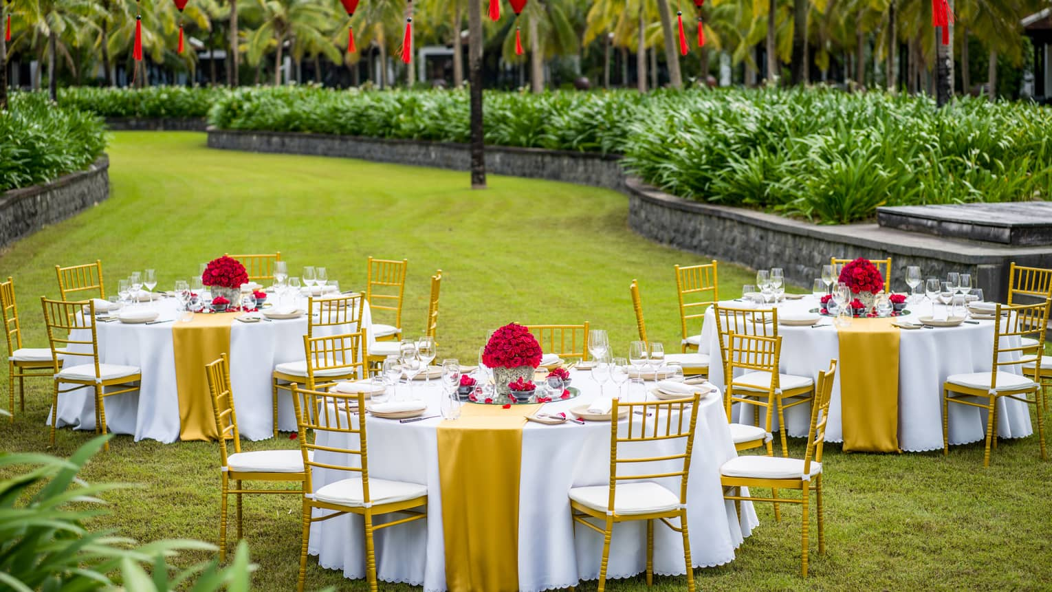 Three tables set out in the lawn with red lanterns for a wedding