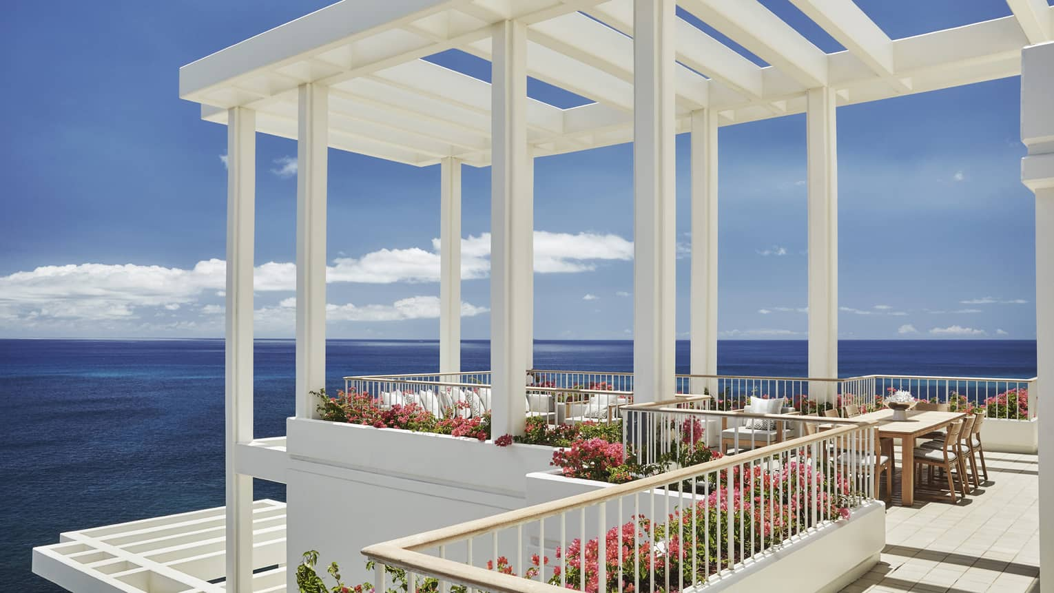 Penthouse Suite patio tables, chairs under white pergola, tropical pink flowers