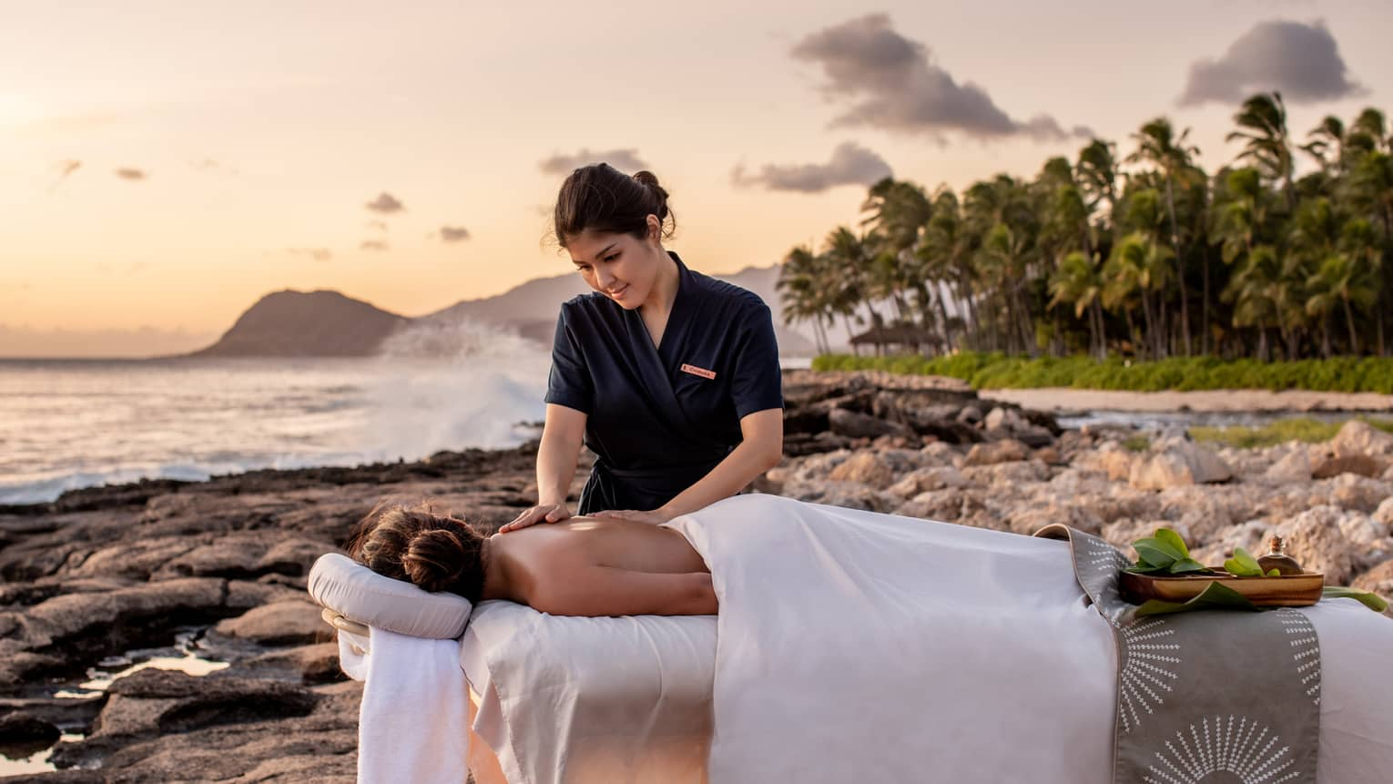 A four seasons guest receives a massage on the beach, as the sun sets in the distance