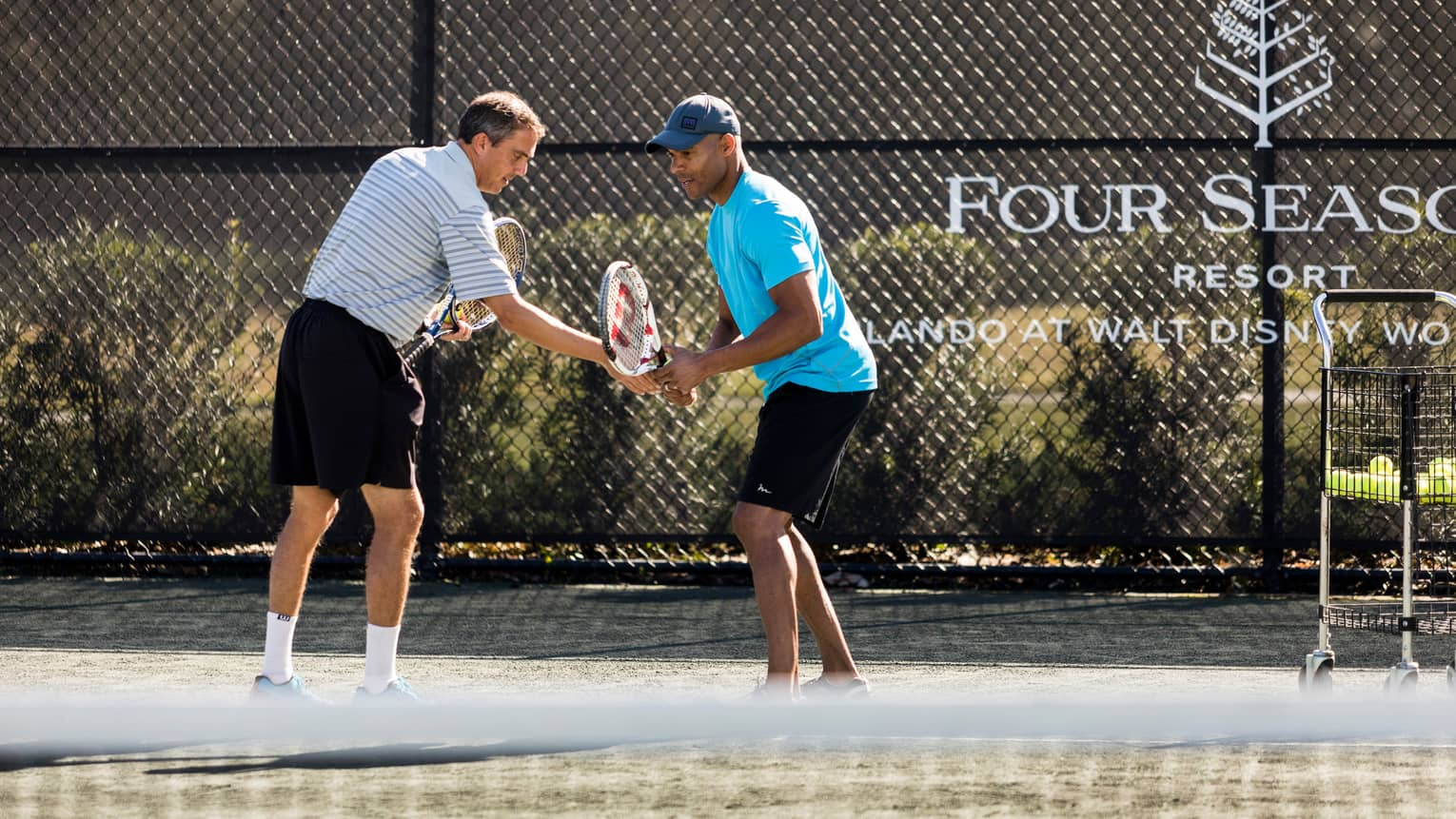 Tennis pro helps man adjust his racket on tennis court by Four Seasons Resort logo on fence