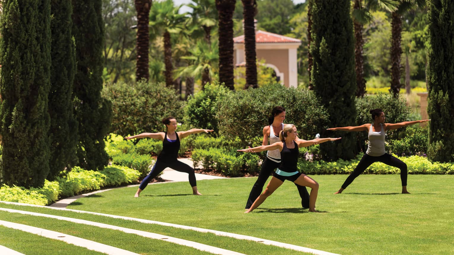 Group of people stand, arms outstretched in yoga poses on green lawn