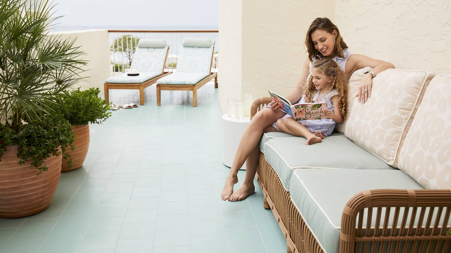 A mother and her daughter read outside in the Ocean Terrace Suite