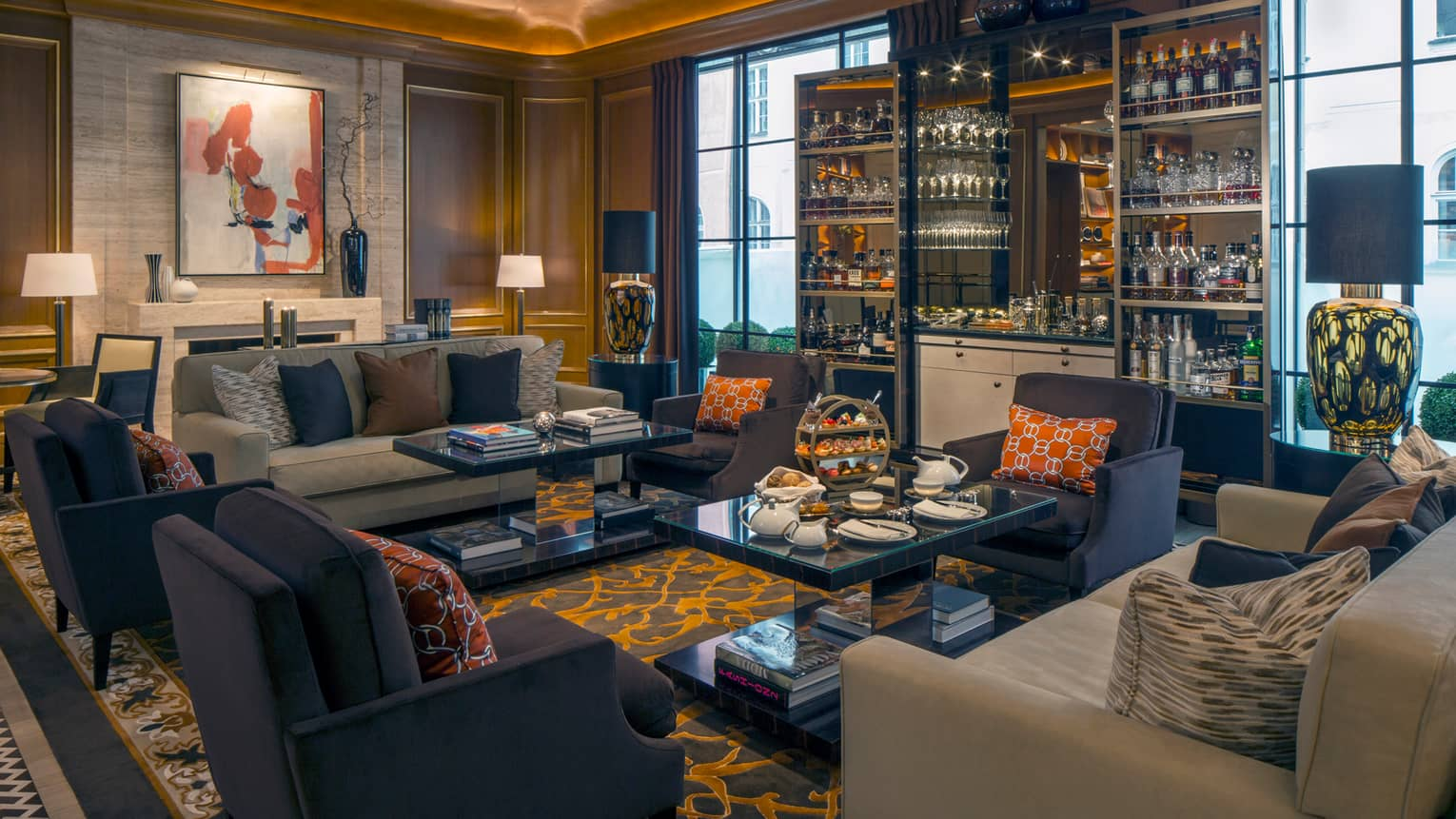 Dark blue armchairs, light sofas around dark glass coffee tables in front of display cabinet with wine, liquor, glasses