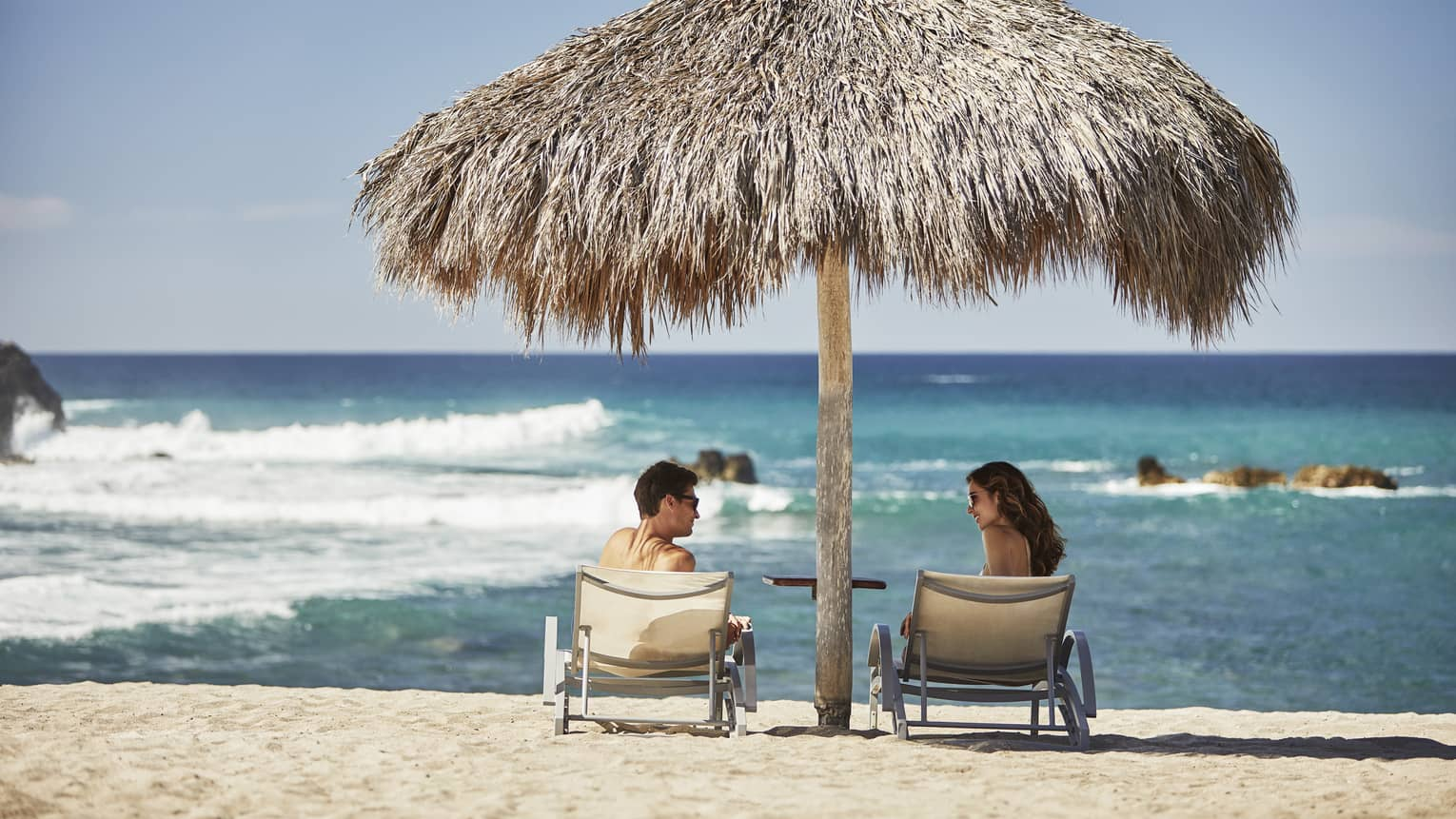 Couple on beach lounge chairs under tiki umbrella by ocean