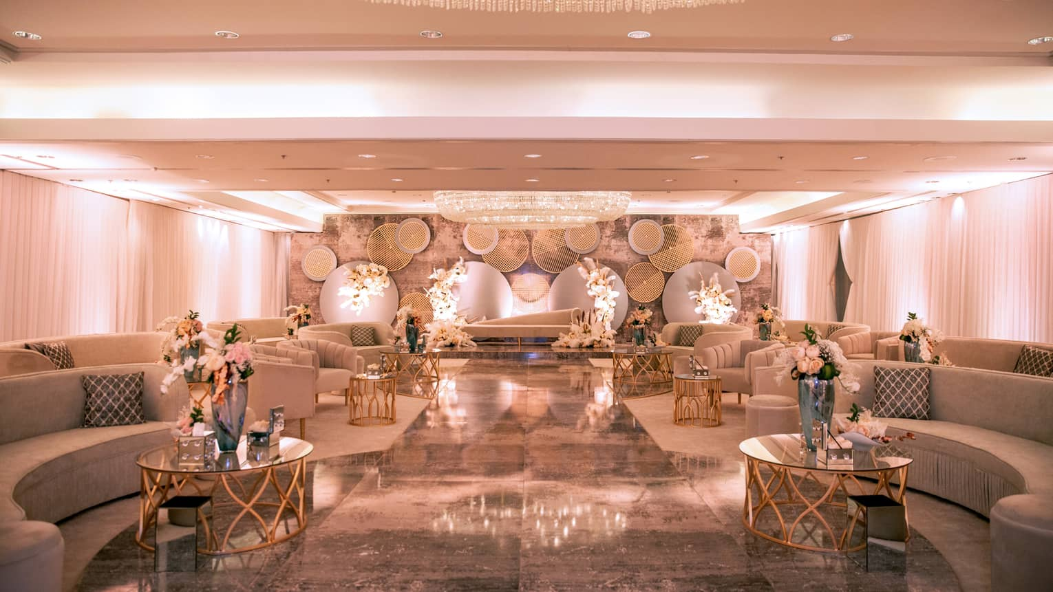 Elegant ballroom with rows of curved sofas, coffee tables and flowers under large dome chandelier