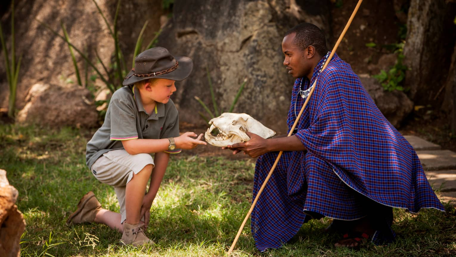 Maasai guide shows large skull to young boy wearing safari hat