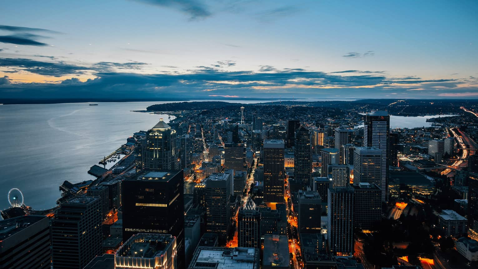 Looking down at buildings, Seattle skyline with lights along Puget Sound at dusk