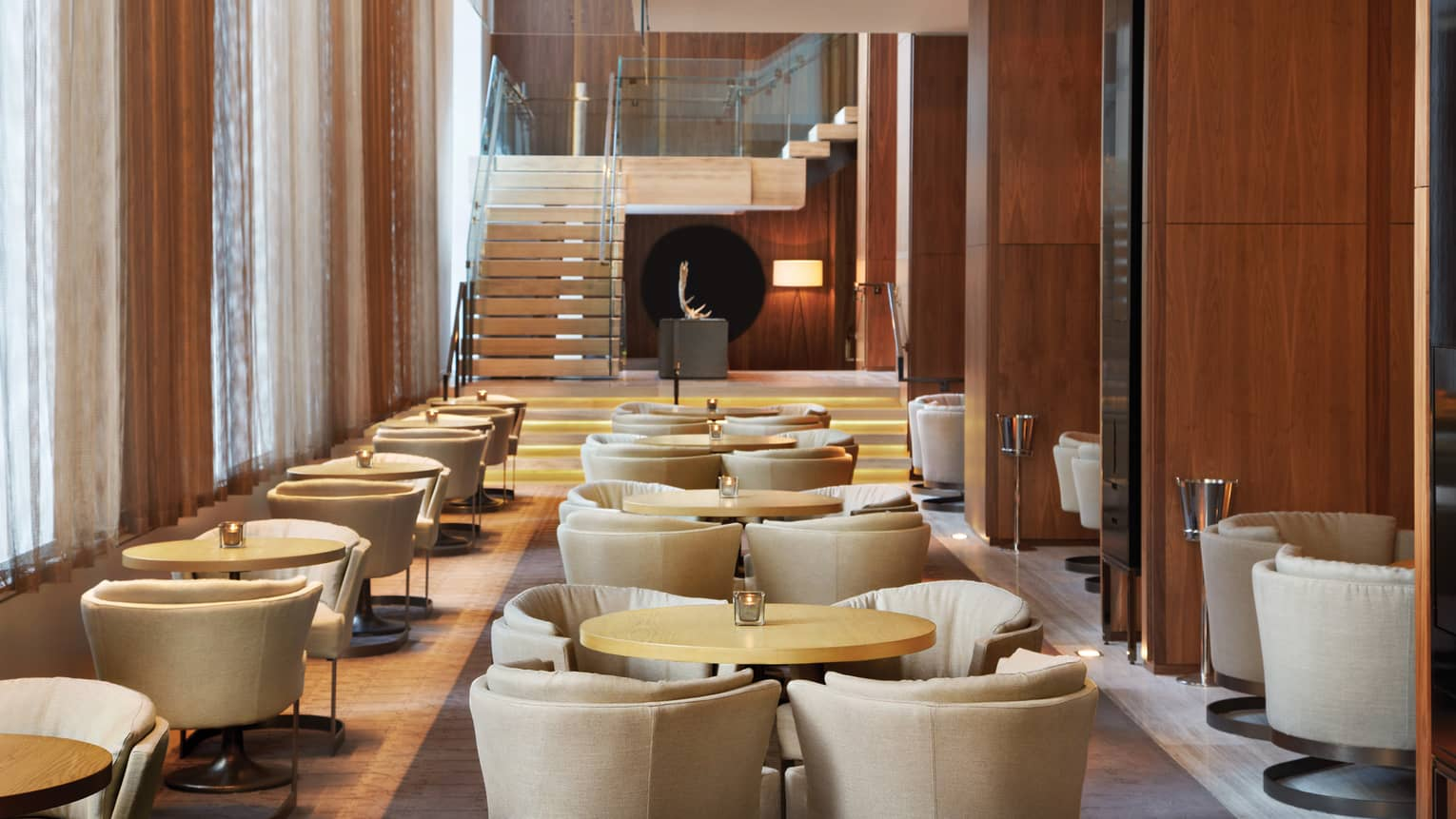 Curved beige chairs around cocktail tables in bright Dbar lounge