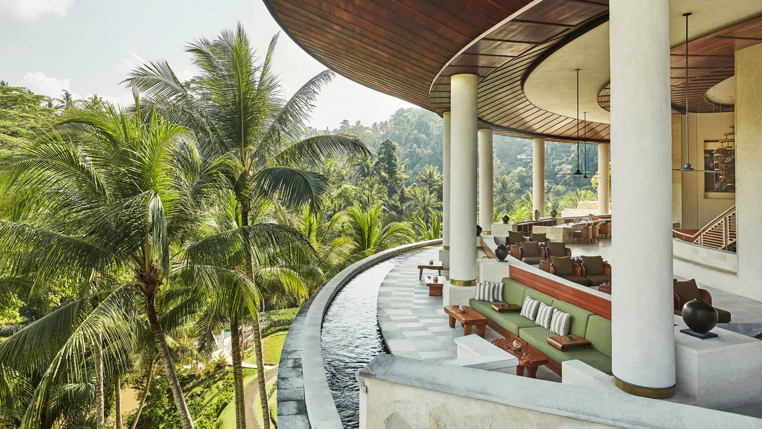 Curved outdoor balcony with water around ledge, green and wood sofas, chairs, vases, large palm leaves outdoors