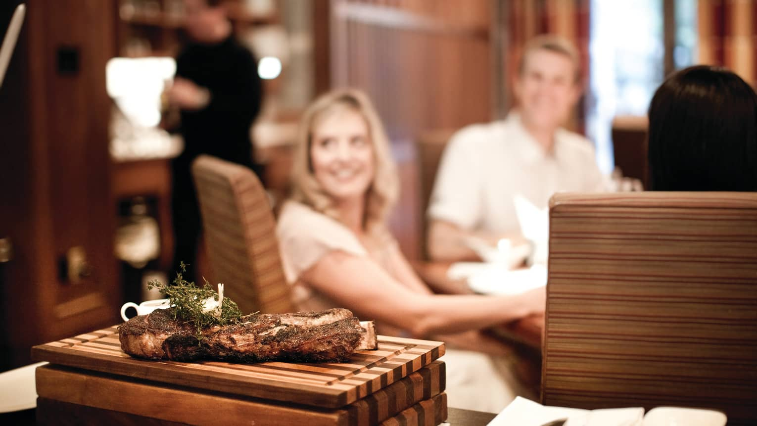 Steak with herb seasoning on wood butcher board, woman and man smiling in background