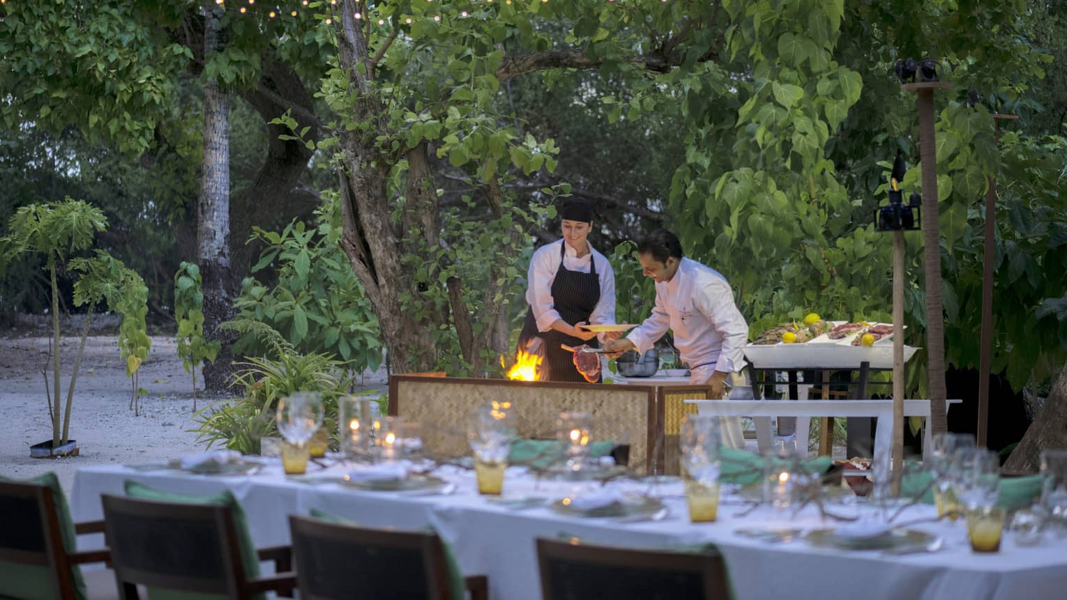 Chefs put large steak on flaming grill by long outdoor dining table, patio lights at night