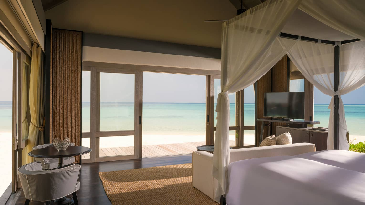 Beach Villa bedroom with white canopy bed by sliding doors to patio, lagoon views