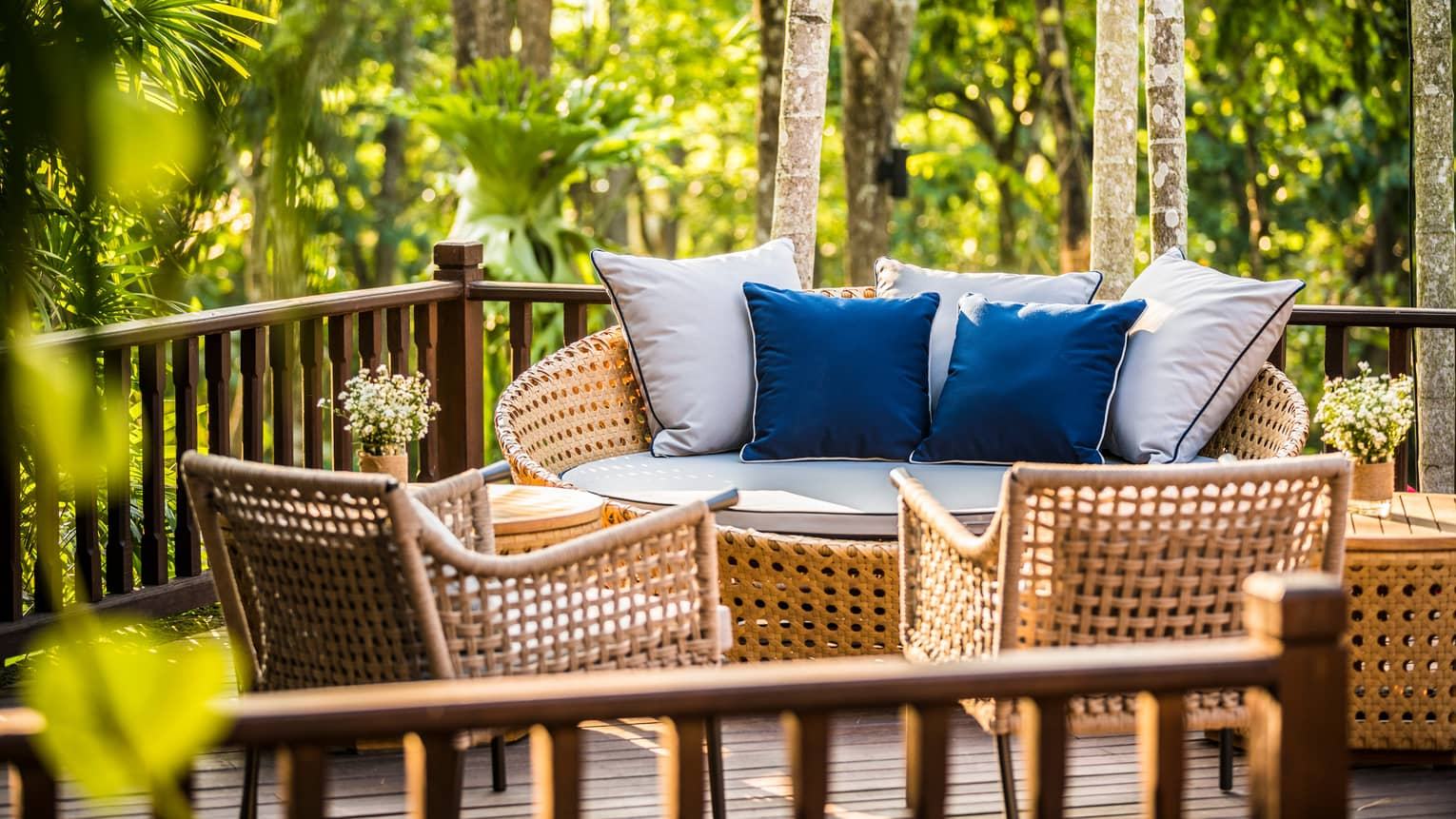Wicker loveseat with white and blue cushions across from chairs on patio