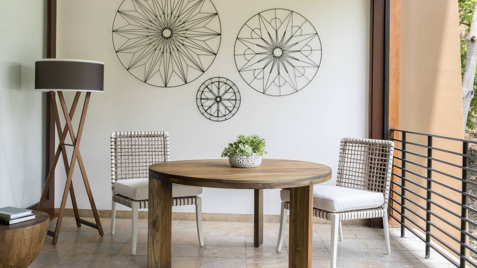 Brisa Room round table with two white wicker chairs on tile terrace, iron decorations on wall