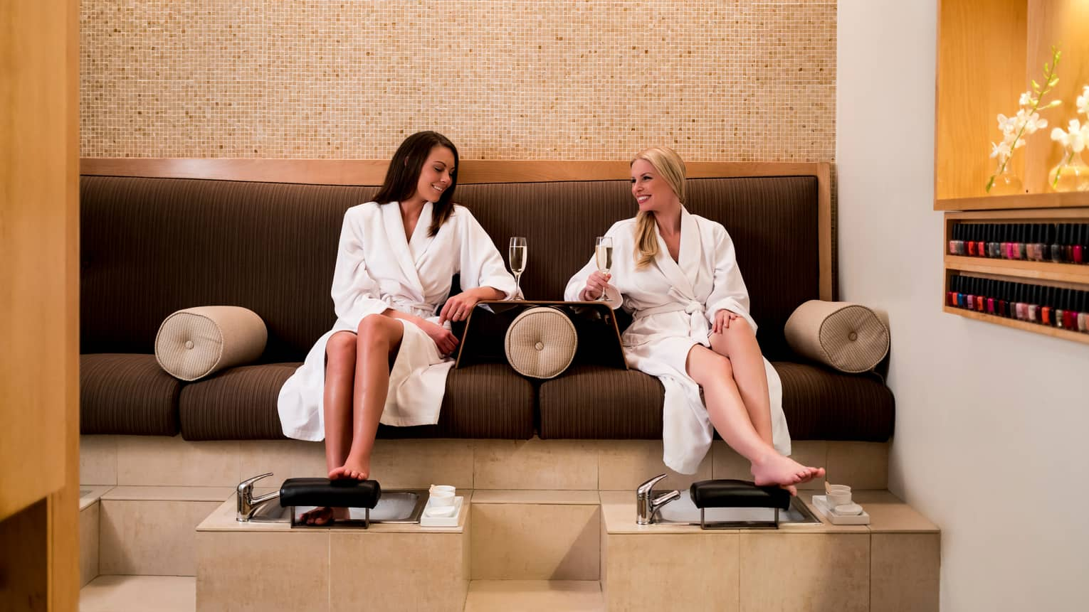 Two women in white bathrobes hold Champagne glasses, sit on spa lounge sofas
