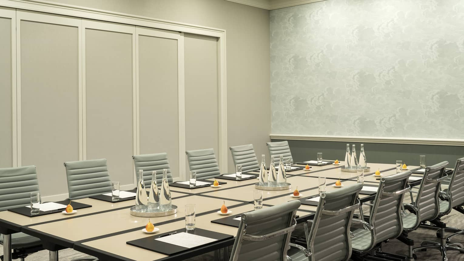 Leather chairs around large rectangular boardroom meeting table with bottles of waters, fresh fruit