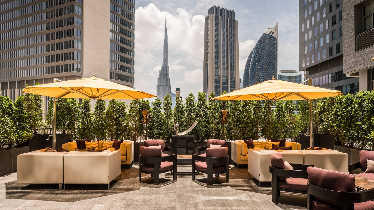 Sunny Penrose Lounge patio with white sofas and chairs, large yellow umbrellas, Dubai skyline