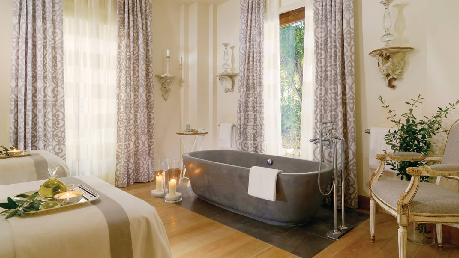 Spa couples massage beds, candles on floor by free-standing tub under tall windows