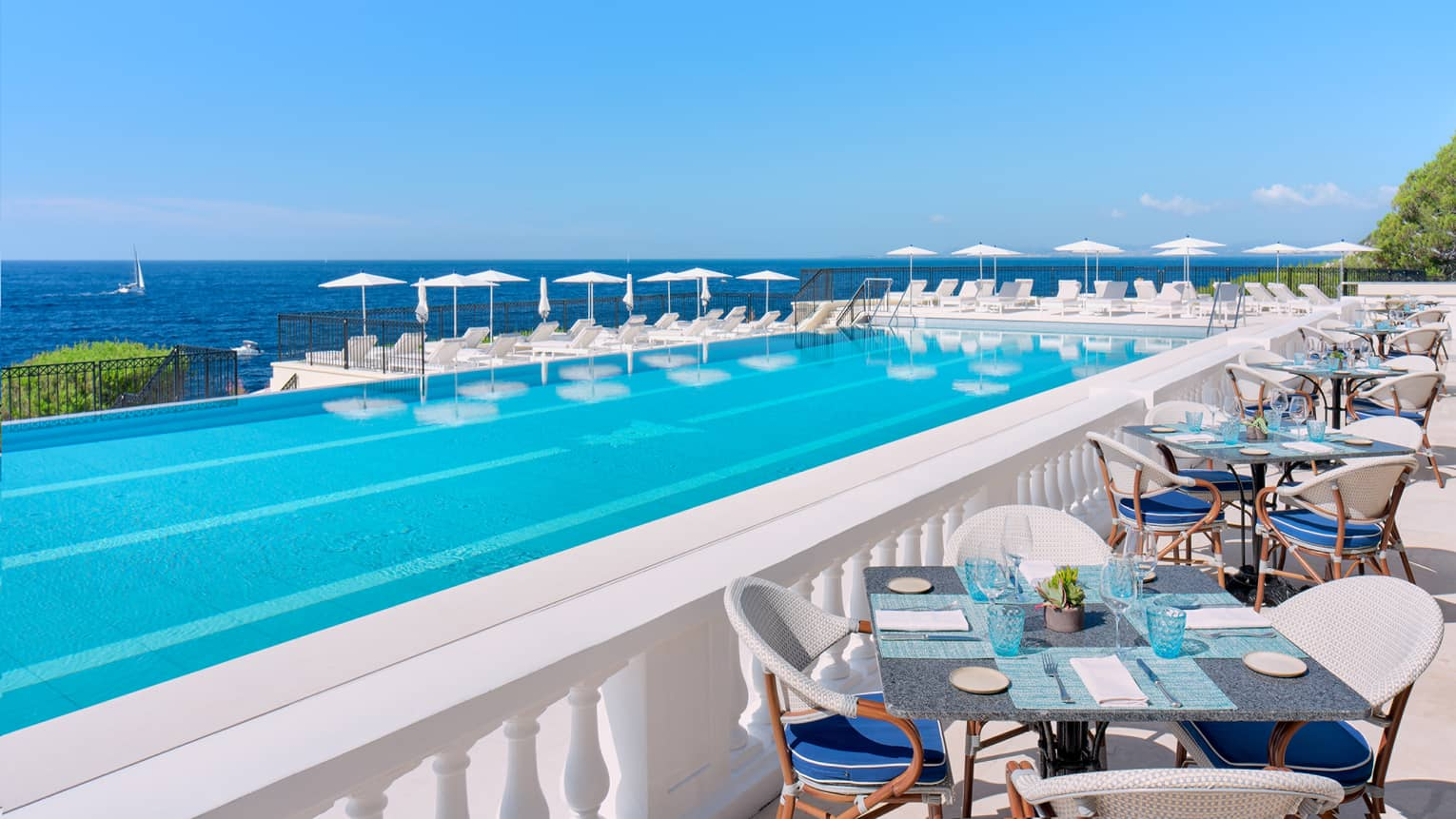 Mediterranean seafront infinity pool surrounded by white tables, lounge chairs, and umbrellas